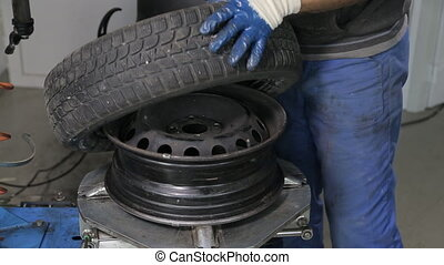 Balancing and Changing tires - Automobile mechanic unscrews...