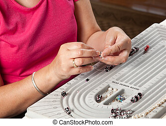 Making bead necklace - Close up of threading beads onto wire...