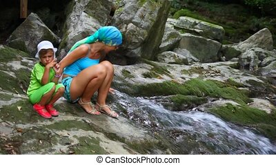 younf woman and little girl near brook running on rock -...