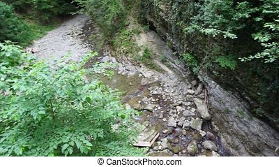mountain river with stones in forest, top view panning from...