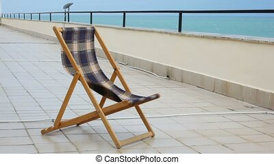 chair standing in verandah of hotel with sea view, material waving by wind