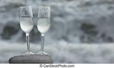 two glasses with wine standing on stone on beach, sea surf in background