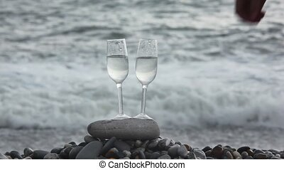 two glasses with wine on stone on beach, couple lifts them...