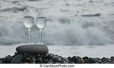 two glasses with wine standing on stone on pebble beach, sea surf in background