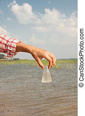Water Purity Test. Hand holding chemical flask with liquid, lake or river in the background.