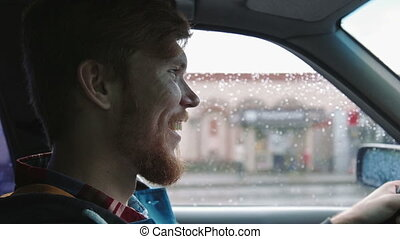 Young happy man driving a car dancing. Inside close up shot