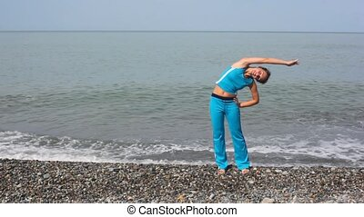 happy smiling young woman exercising on beach, sea in background