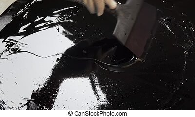 Builder aligns spatula bitumen mastic - Work with a spatula...