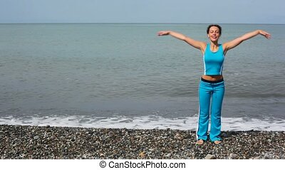 happy young woman exercising on beach, sea in background