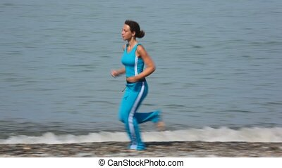 young woman in tracksuit running on pebble coast, sea in background