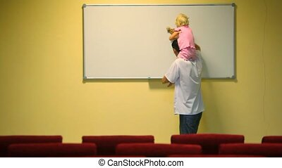 man holding little girl on shoulders cleans whiteboard in lecture room