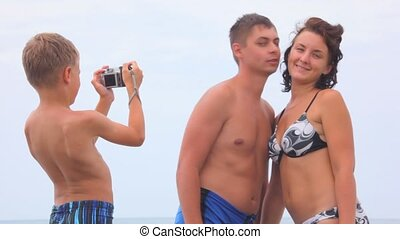boy photographing man and woman dressed in swimsuit on beach