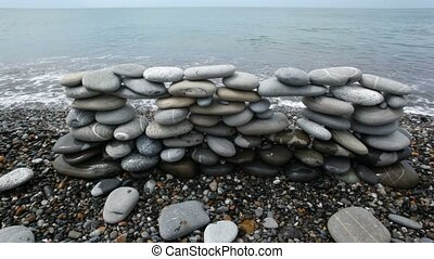wall of stones on beach, sea surf in background