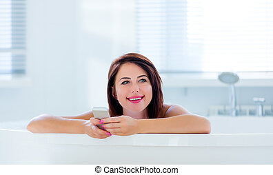 young woman in bath with phone - photo of the beautiful...