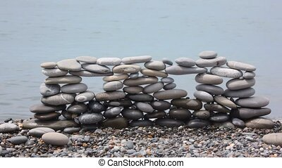 wall of stones on pebble beach, blue sea surf in background