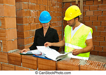 Constructions workers looking on house plans - Constructions...