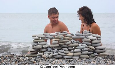 happy man and woman building wall of stones on beach, sea surf in background