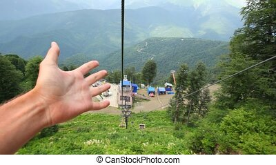 moving funicular above forest in mountains, two hands giving...