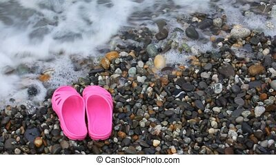 childrens pink slippers on pebble beach with sea surf