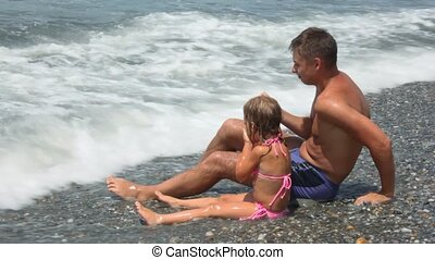 man with little girl has fun sits on pebble beach under sea surf waves