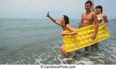 two womans and man holds inflatable mattress stands on beach
