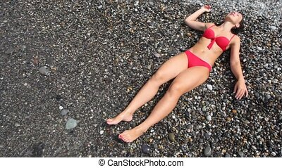 woman dressed in swimsuit lying on pebble beach with sea...