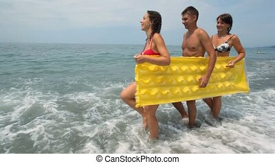 two womans and man holds inflatable mattress walking on beach