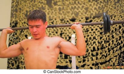 young athletic man in gym doing weight lifting sitting on...