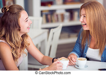 Joyful mother and daughter drinking coffee