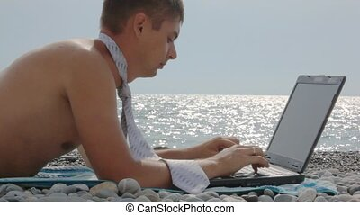 man dressed in swimming trunks and tie lying on beach with notebook against sea