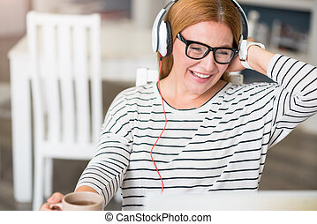 Cheerful woman listening to music - Feel the beat. Cheerful...