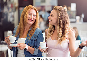 Cheerful mother and daughter drinking coffee