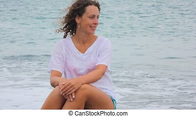 smiling young woman sitting, hair swaying by wind, waving sea in background