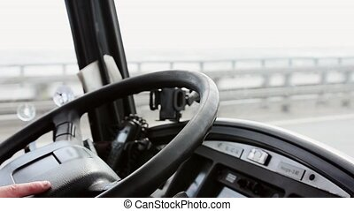 Hand of driver on steering wheel of bus moving on motorway focus in. Day