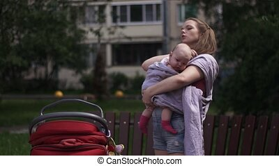 Young mother put on baby sling hold little child Baby...