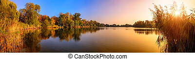 Lake sunset panorama in gold and blue - Panorama of a...