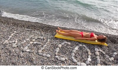 young woman lying on inflatable mattress, BEACH stone...