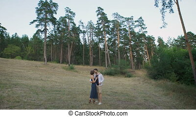 Beautiful man and woman embracing standing in a clearing in the middle of a pine forest.