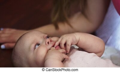 Young mother lie on floor speak with little baby, hold hands in mouth. Apartment