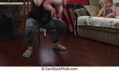 Young mother make squats with baby in hands. Son sitting on sofa. Apartment