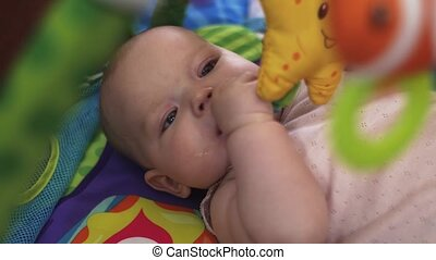 Little baby lie in crib playing with toys. Child. Cute. Family. Motherhood.
