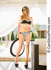 Sexy young blonde in swimming suit posing with a hat