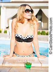 Portrait of a nice blond woman posing in the swimming pool