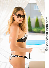 Young curly blond woman in swimming suit and sunglasses...