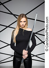 Portrait of serious blond woman posing with sword