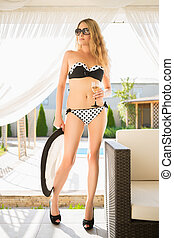 Young leggy blond woman in swimming suit posing with a drink...