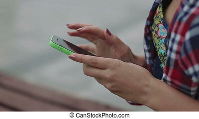 hands Young woman with smartphone sitting on a bench in the...