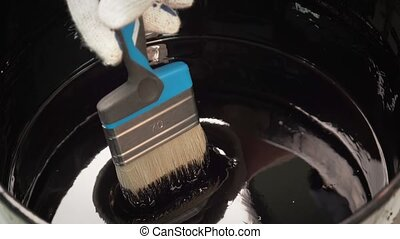painters brush dipped in a bowl of thick bitumen - Paint...