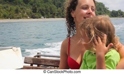 happy young woman with little girl sitting in going cutter