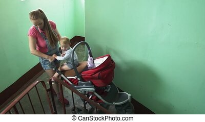 Young mother put down red baby carriage from stairs. Motherhood. Little boy.